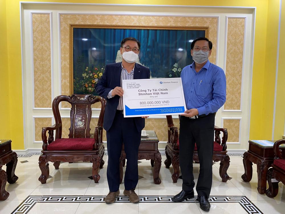 Ông Oh Tae Joon - Phó tổng giám đốc Shinhan Finance trao biểu trưng số tiền đóng góp 800 triệu đồng cho đại diện Ủy ban Mặt trận Tổ quốc Việt Nam TP.HCM ngày 31/3/2020. Ảnh: Shinhan Finance