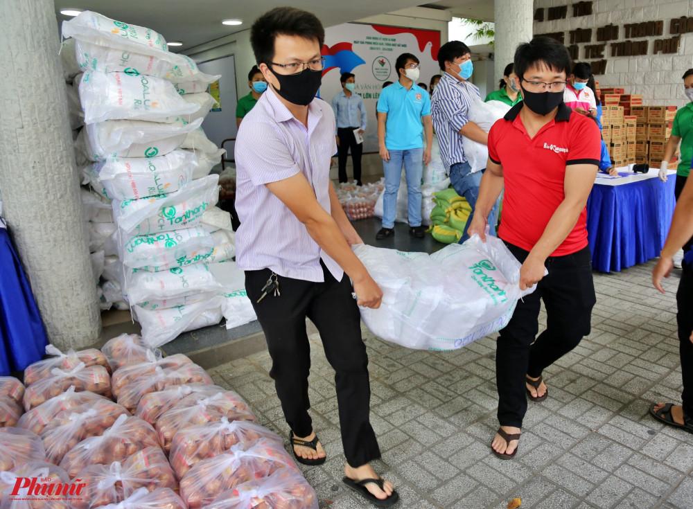 Các tình nguyện viên vận chuyển gạo lên xe chuyển đến người dân 24 quận huyện trên địa bàn thành phố