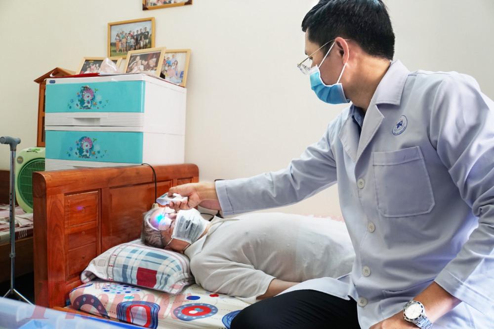 Trước khi khám bệnh, bác sĩ Nguyễn Minh Quân đo thân nhiệt cho ông C., hướng dẫn ông khai báo y tế cũng như các phương pháp phòng chống COVID-19