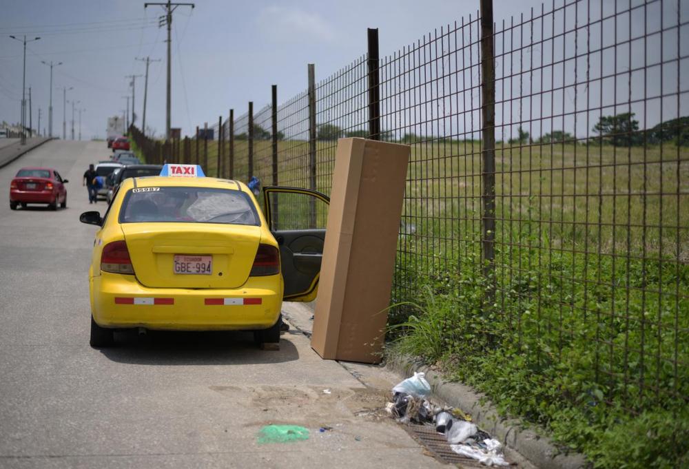 Quan tài các tông rỗng đặt bên cạnh hàng rào một nghĩa trang khi dịch bệnh COVID-19 gây nên tình trạng thiếu quan tài ở thành phố Guayaquil, Ecuador - Ảnh: Reuters