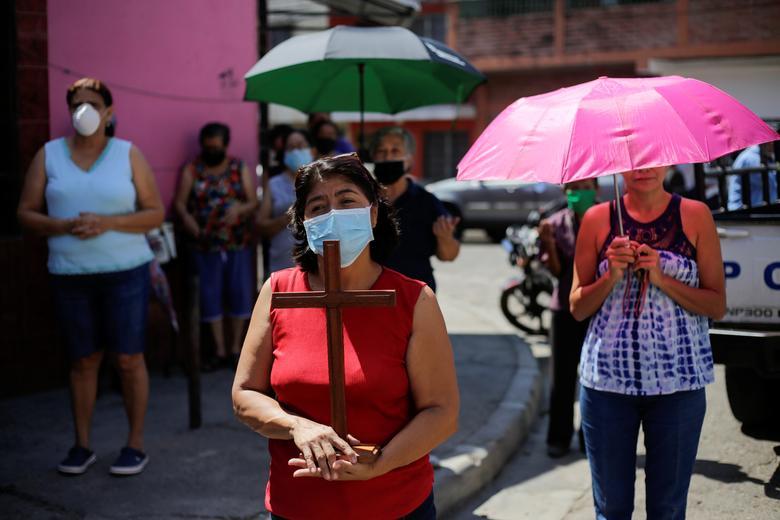 Người dân ở Tegucigalpa, Honduras đeo khẩu trang, đứng xa nhau để thực hiện nghi thức cầu nguyện khi một đoàn xe rước đi ngang vào ngày thứ sáu tuần thánh.