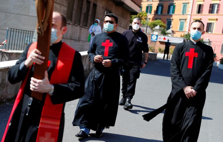 Một giáo sĩ mang thánh giá đến bên ngoài bệnh viên San Giovanni (Rome, Ý) để ban phước lành cho đột ngũ nhân viên y tế hôm 10/4.