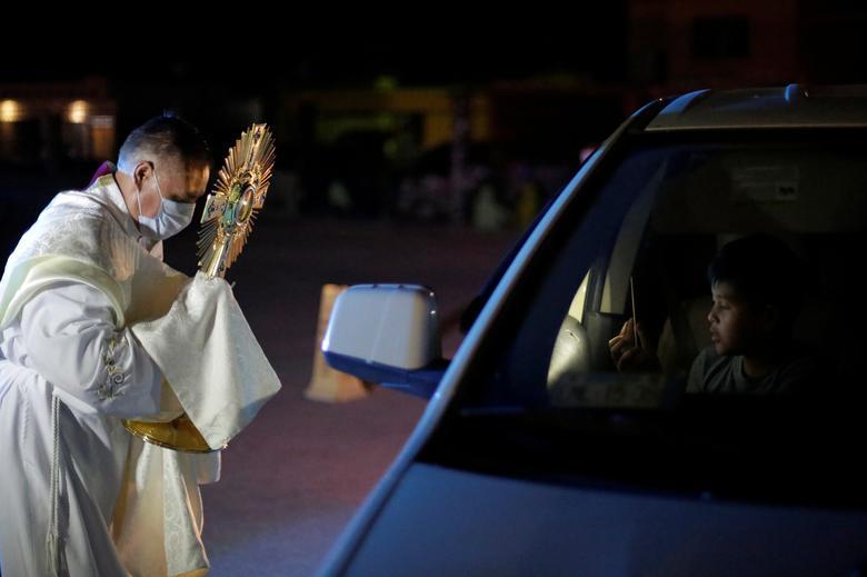 Linh mục Jesus Tovar ban phước lành cho người lái xe trong ngày thứ năm tuần thánh tại Ciudad Juarez, Mexico.