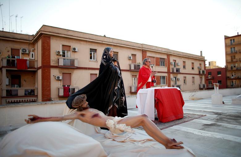 Linh mục Don Amedeo Basile dẫn đầu đoàn rước Đàng thánh giá trên sân thượng của nhà thờ Maria SS Addolorata để người dân địa phương tham gia từ ban công và cửa sổ
