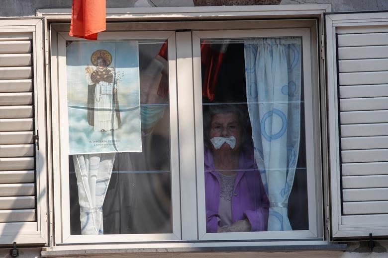 Một cụ bà đang quan sát cây thánh giá được trưng bày bên ngoài nhà thờ Santa Maria della Sanita