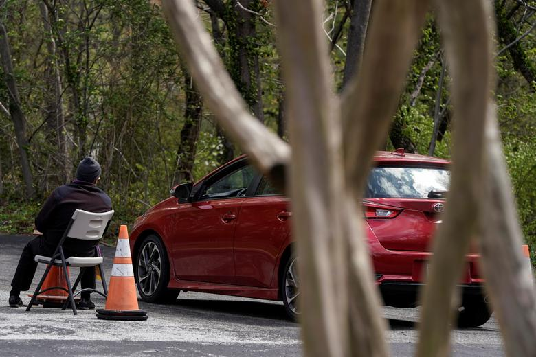 Cha Matthew Fish, mục sư của Nhà thờ Công giáo Holy Family đang lắng nghe lời thú tội của một giáo dân từ trong xe ôtô
