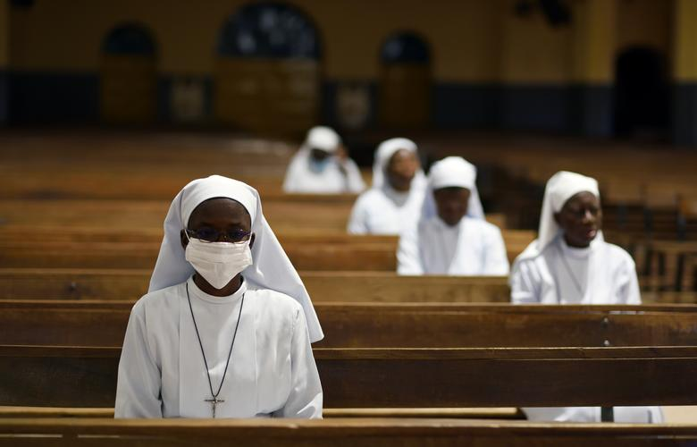 Nữ tu đeo khẩu trang, tham dự thánh lễ tại một nhà thờ vắng lặng ở Ouagadougou, Burkina Faso.