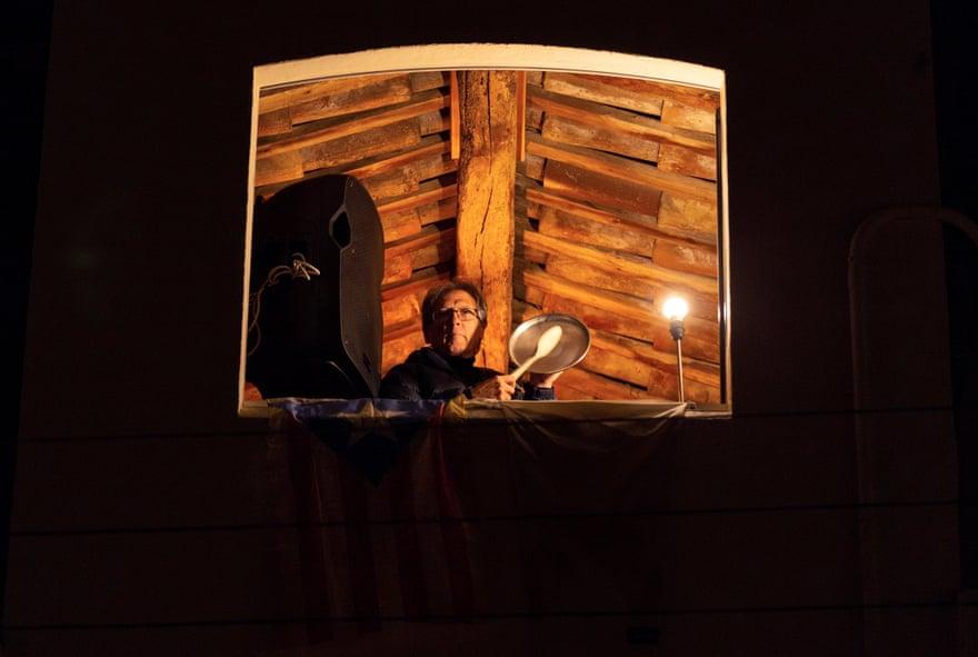 Một người đàn ông ở Tây Ban Nha chơi nhạc từ cửa sổ trên gác cao.