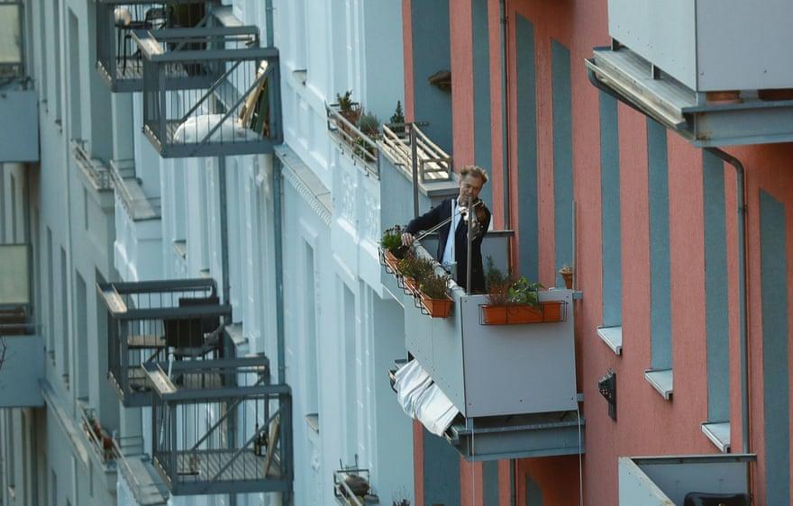 Người đàn ông ở Đức mê mải với cây đàn violon tại ban công nhà.