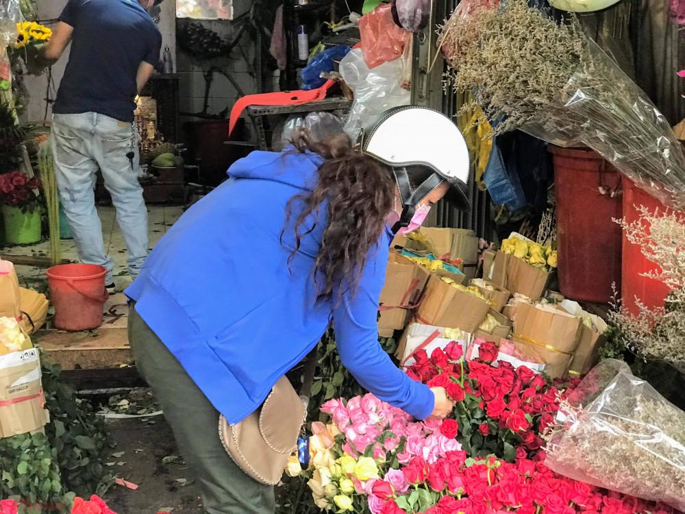 """Cũng theo anh, một nguyên nhân khiến giá hoa tại các shop, sạp tại đây thường cao hơn các lề đường, vỉa hè (hiện có nơi mức giá 50.000 đồng/50 bông) vì hiện tại đang cao điểm dịch bệnh COVID-19, cách ly toàn xã hội nên cung cầu bị tác động, hiện nhu cầu đang giảm, không có người mua, xe hàng thậm chí 3-5 ngày mới chở hoa về TPHCM một lần, bình thường đi riêng mỗi xe tải toàn hoa hồng thì nay hoa bán ít lại nên đợi đi chung đợt với các loại hoa khác như cúc, ly, hướng dương,… Còn các điểm bán hoa vìa hè trong mùa dịch có nơi bán rẻ có thể là hoa từ Đà Lạt nhiều nên buộc các thương lái, nhà vườn """"đánh"""" vào TPHCM bán tháo bán rẻ lại, tuy nhiên hoa đặc thù của hoa là sáng bán không hết tối thành rác… nên buộc người bán lề đường phải xả rẻ, bán như cho."""