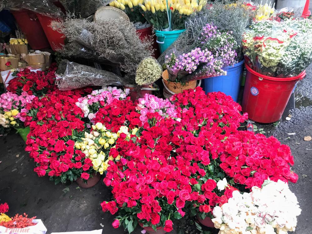 """Chủ một shop hoa tên Tuấn – kinh doanh hoa lâu năm tại khu vực chợ này cho hay sở dĩ giá hoa hồng cao là do hoa anh lựa chọn từ trong bó lớn 50 bông, những bông đạt được chọn phải là loại to, đều, đẹp, không dập, héo,… hiện anh này bán với mức giá lẻ là 5.000 đồng/bông hồng đỏ, 8.000 đồng/bông loại hồng (màu hồng phấn, xanh nhạt,…).   """"Mức giá lẻ cao là do ngoài công lựa, tỉa lá và gai, thêm nhân công thì loại hồng chỗ shop bán chủ yếu là hàng tuyển, sẽ chưng được lâu, đẹp hơn các loại hoa bán bên trong chợ"""", anh Tuấn cho hay."""