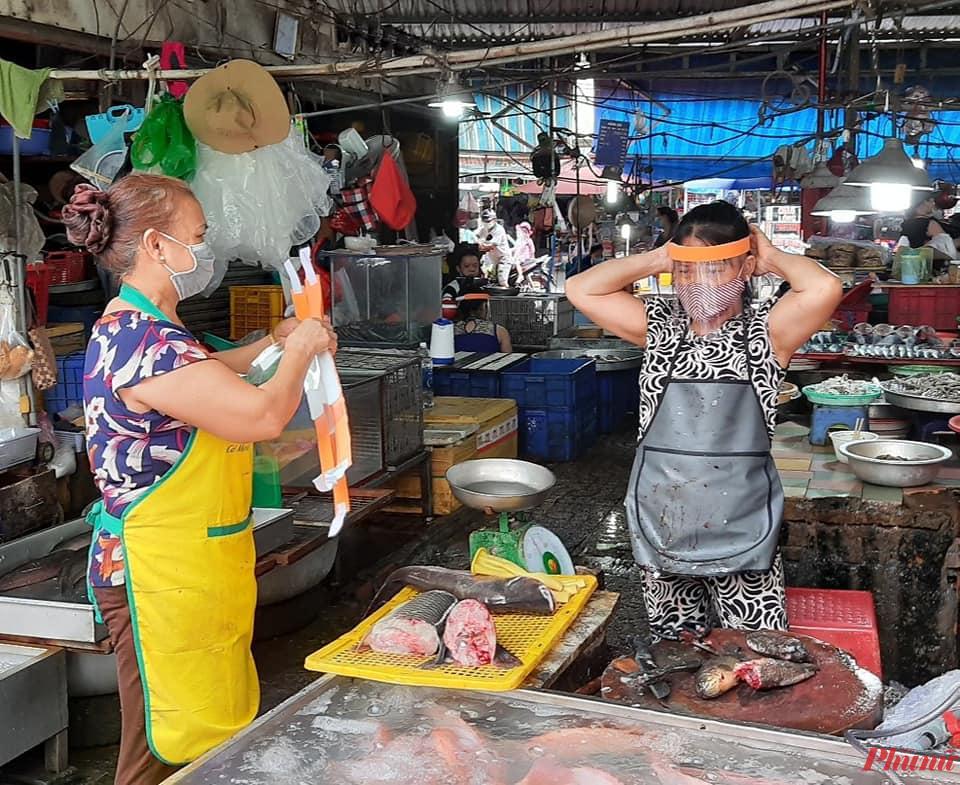 Tiểu thương chợ Linh Trung nhận tấm che mặt chắn giọt bắn phòng dịch COVID-19.