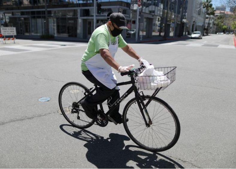 Một người giao thực phẩm bằng đạp xe trên một con đường vắng do cách ly xã hội tại Beverly Hills, California, Hoa Kỳ, ngày 15/4. Ảnh: Reuters
