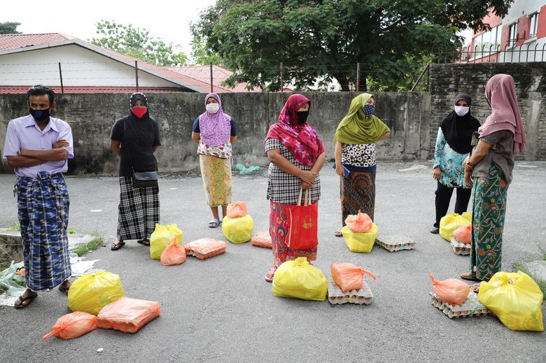 Nhóm người tị nạn mang khẩu trang, xếp hàng chờ được phân phát những món hàng do các tình nguyện viên gửi tặng tại Kuala Lumpur, Malaysia vào hôm 7/4.