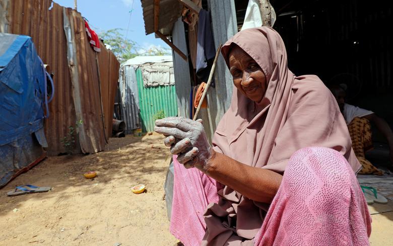 Một người phụ nữ Somali phải dùng tro và đất để rửa tay trong một trại tị nạn ở Mogadishu, Somali.
