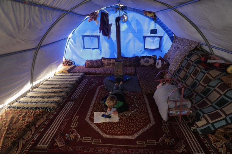 Mahmoud Abdel Hadi (8 tuổi) làm bài tập được giao qua điện thoại di động của phụ huynh trong một căn lều tị nạn ở trại Atmeh, gần biên giới Thổ Nhĩ Kỳ, Syria.
