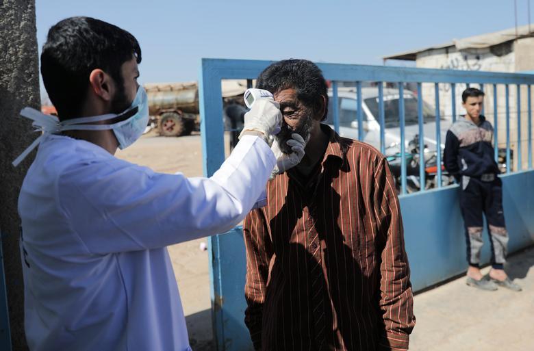 Nhân viên y tế đo thân nhiệt cho một người di cư tại Azaz, Syria - như một nỗ lực của chính quyền để giảm nguy cơ lây lan dịch bệnh trong cộng đồng.