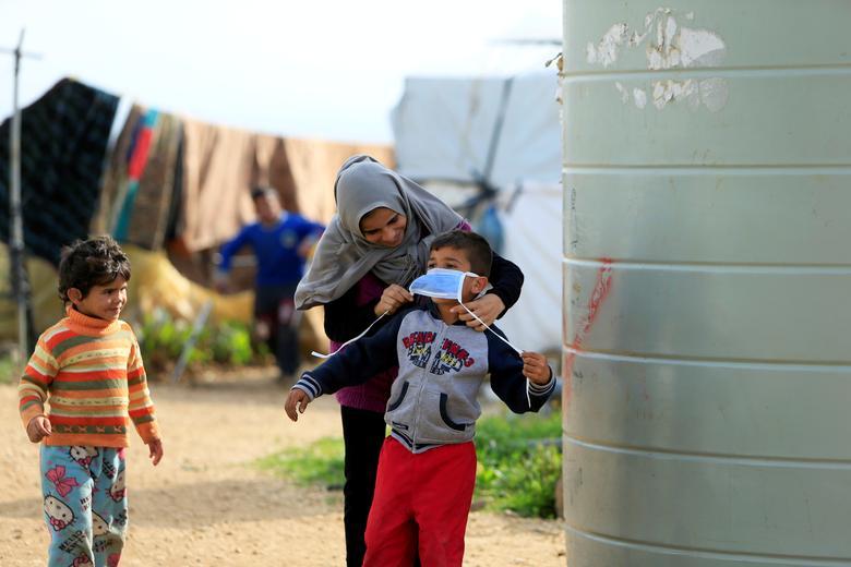 Một phụ nữ đeo khẩu trang cho đứa bé để tránh bị lây nhiễm bệnh trong trại tị nạn ở All-Wazzani, miền nam Li-băng.