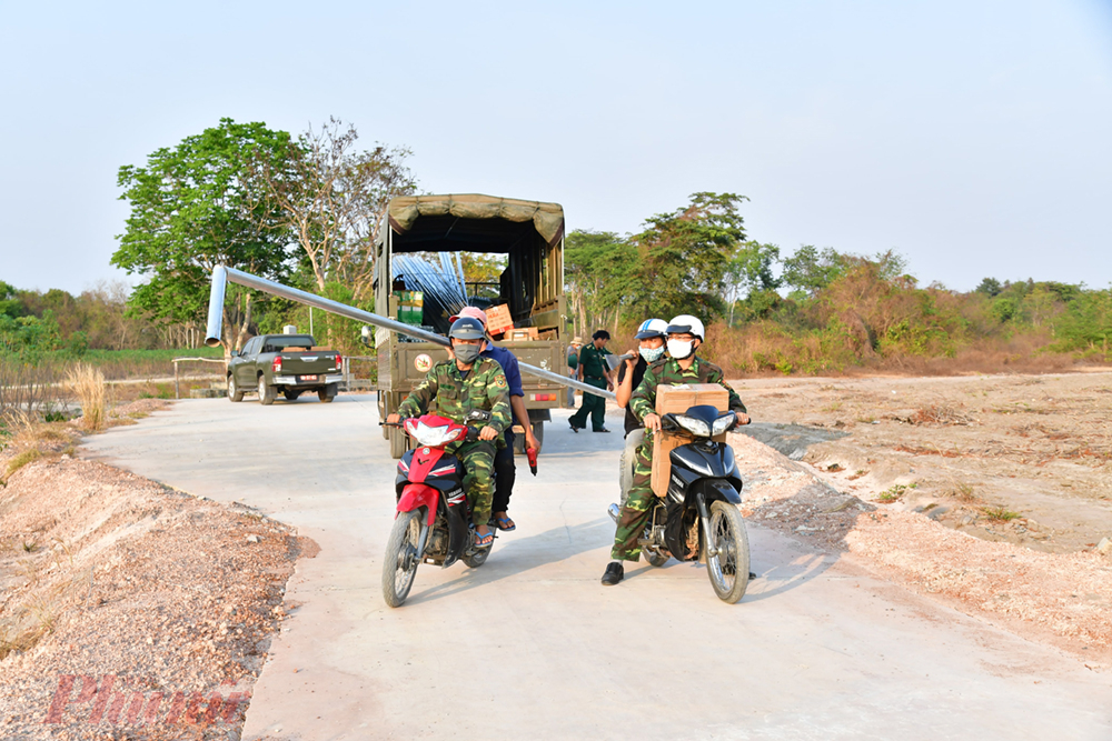 Các chiến sĩ biên phòng trung chuyển vật tư bằng xe gắn máy tới những điểm chốt nằm trong rừng - nơi xe ô tô không vào được