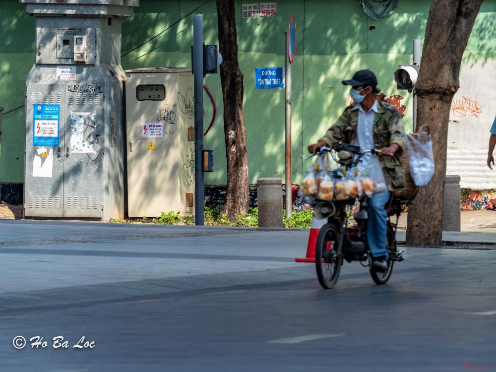 Trên đường phố vắng người, tiếng rao của những người bán bánh mì dạo càng thêm nao lòng. Ảnh: Hồ Bá Lộc.