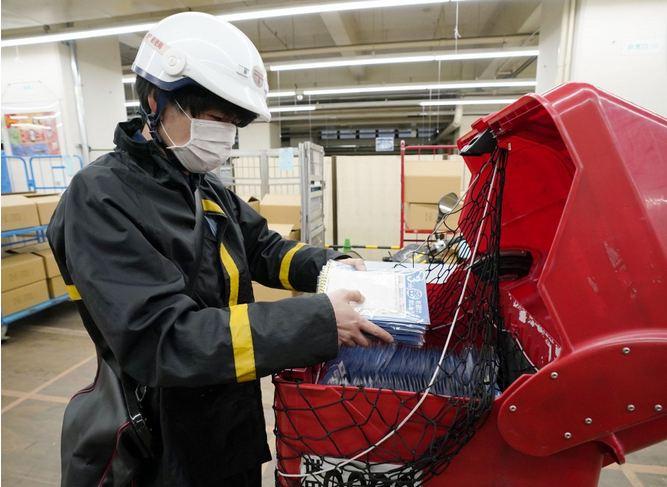 Nhân viên bưu chính Nhật đi giao khẩu trang. Ảnh: Kyodo News