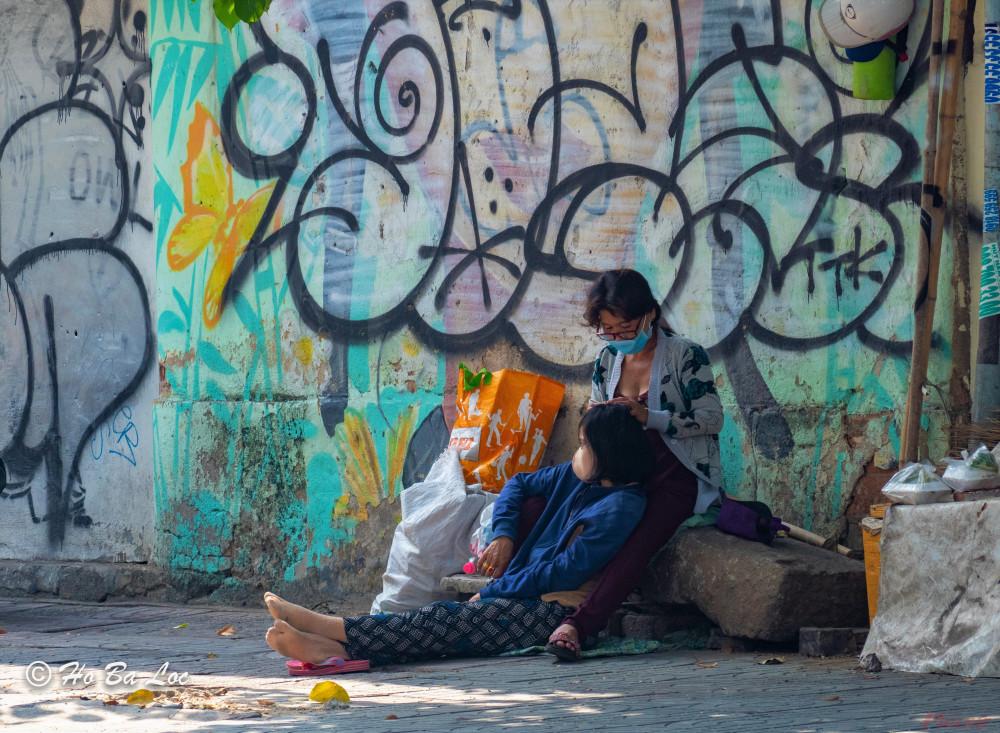 Hai người phụ nữ làm nghề thu mua ve chai ngồi nghỉ mệt ngay trên lề đường sau một ngày lê bước khắp nơi nhưng không mua được gì nhiều. Ảnh: Hồ Bá Lộc