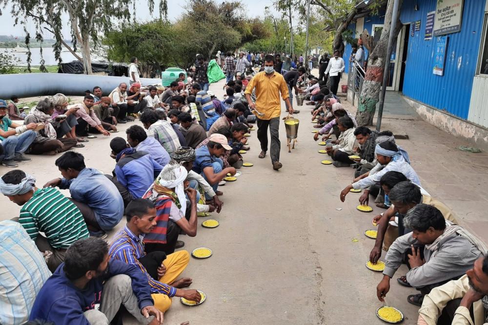 Người nghèo chờ nhận thức ăn tại một trung tâm hỗ trợ của chính phủ ở New Delhi, Ấn Độ.