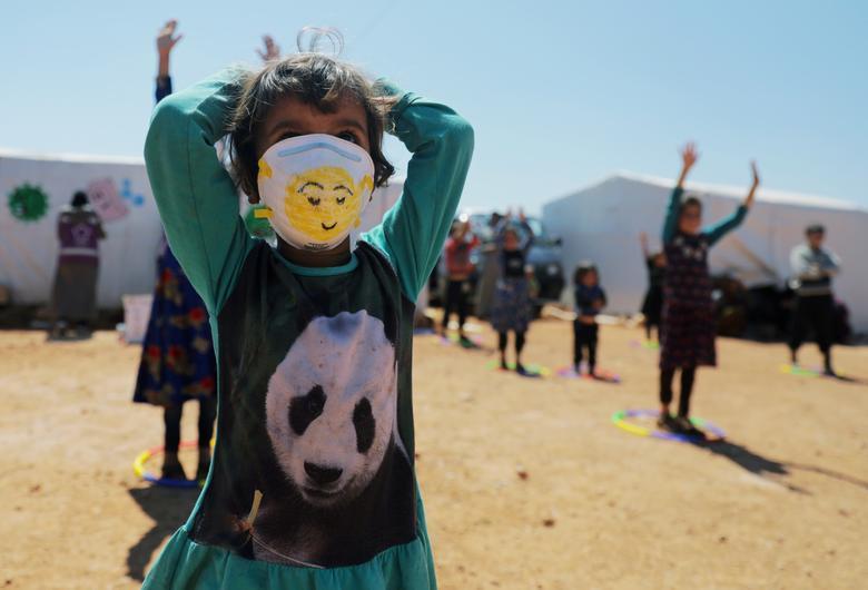 Một bé gái tị nạn đang đeo khẩu trang và thực hiện một số