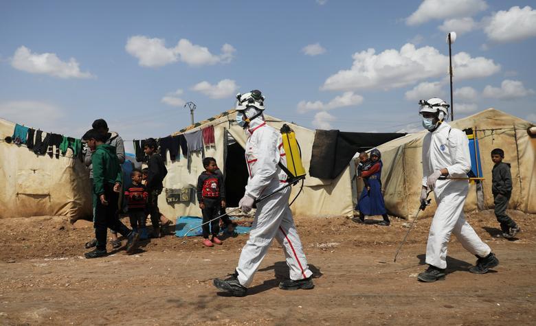 Các thành viên lực lượng dân phòng Syria phun khử trùng cho một trại tị nạn ở Azaz, Syria.