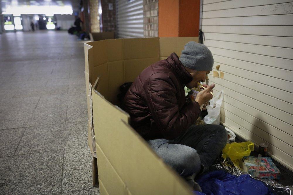 """Một người vô gia cư ăn bữa tối muộn trong """"nhà"""" các-tông ở ga Shinjuku, Tokyo. Ảnh: AP"""