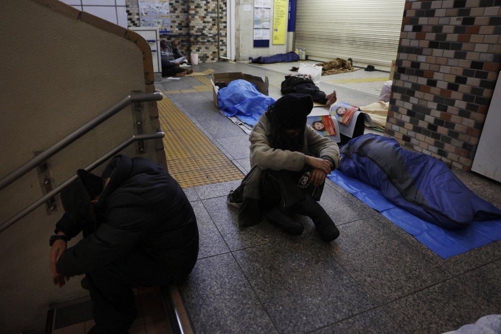 Người vô gia cư ngủ trên sàn bê-tông ở ga Shinjuku, Tokyo. Ảnh: AP