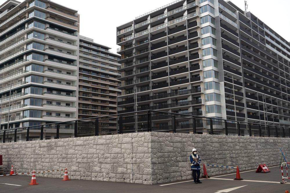 Một bảo vệ đứng trước các tòa nhà tại làng vận động viên dành cho Thế vận hội Tokyo 2020. Ảnh: AP