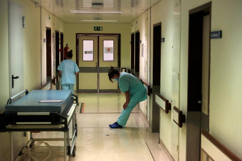 Một nhân viên y tế tranh thủ dựa lưng vào tường để nghỉ ngơi sau khi đièu trị cho bệnh nhân trong bệnh viện Santa Maria ở Lisbon, Bồ Đào Nha.