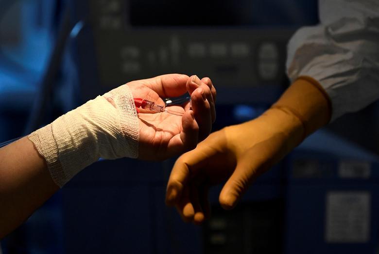 Một bệnh nhân đang cố đưa tay ra để nắm tay bác sĩ trong phòng điều trị tích cực ở chăm sóc đặc biệt tại bệnh viện Circolo ở Varese, Ý