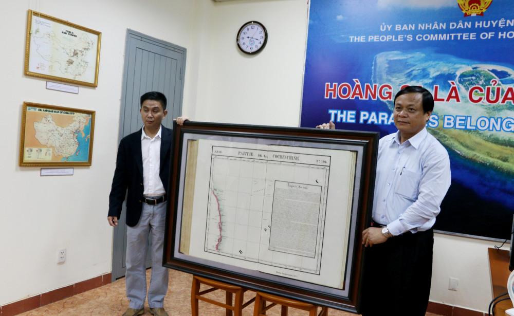Chủ tịch UBND huyện Hoàng Sa Võ Ngọc Đồng (bìa phải) trong một lần tiếp nhận tư liệu khẳng định chủ quyền Hoàng Sa của Việt Nam