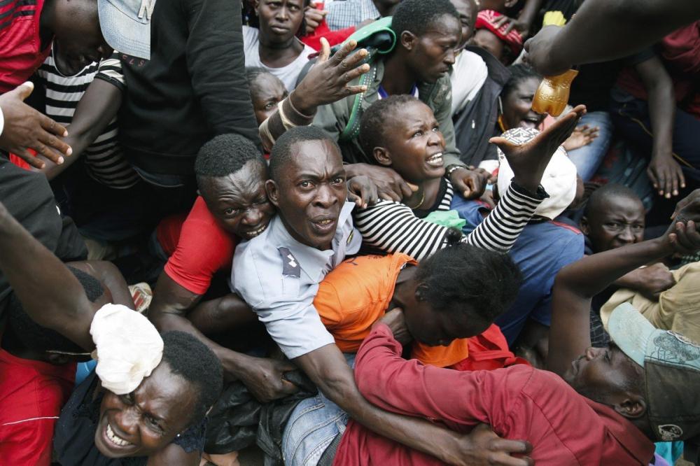 Nhiều người dân khu ổ chuột Kibera ở Kenya bị thương vì trúng hơi cay khi tranh cướp thực phẩm do các nhà hảo tâm cứu trợ - Ảnh: AP
