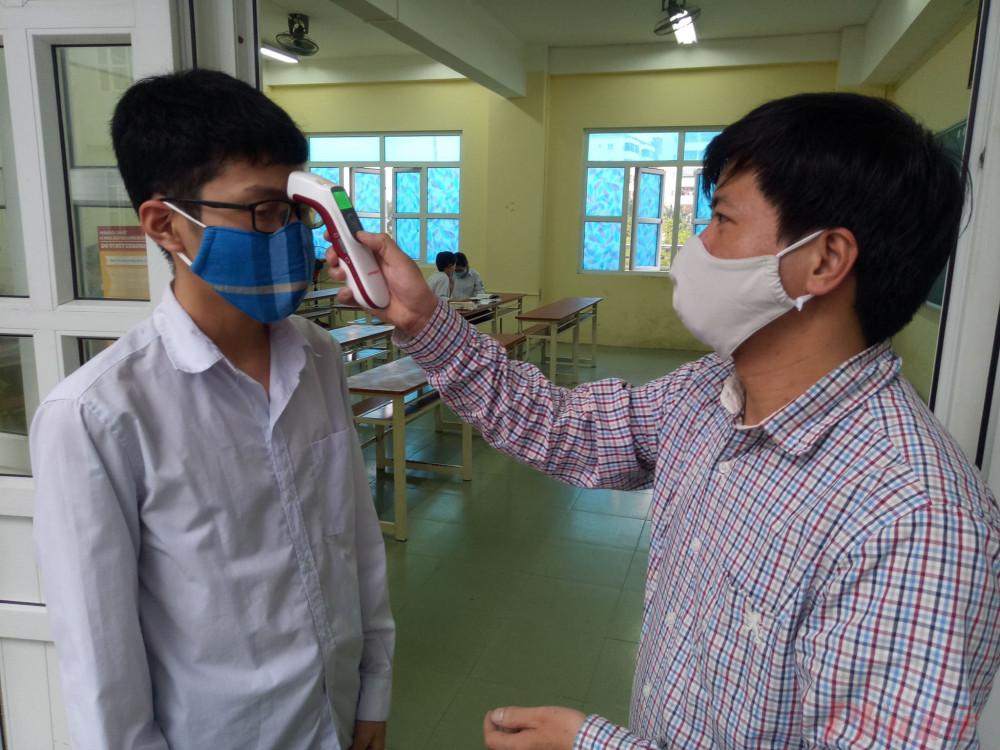 Giáo viên kiểm tra nhiệt độ học sinh ngay cửa lớp