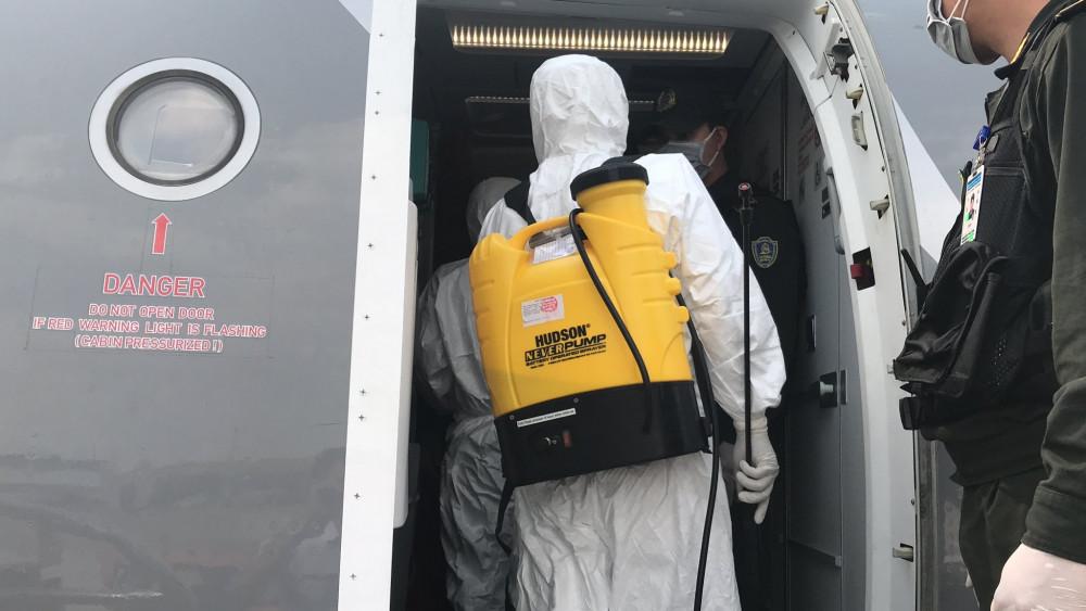 Nhân viên y tế khử khuẩn trên máy bay.