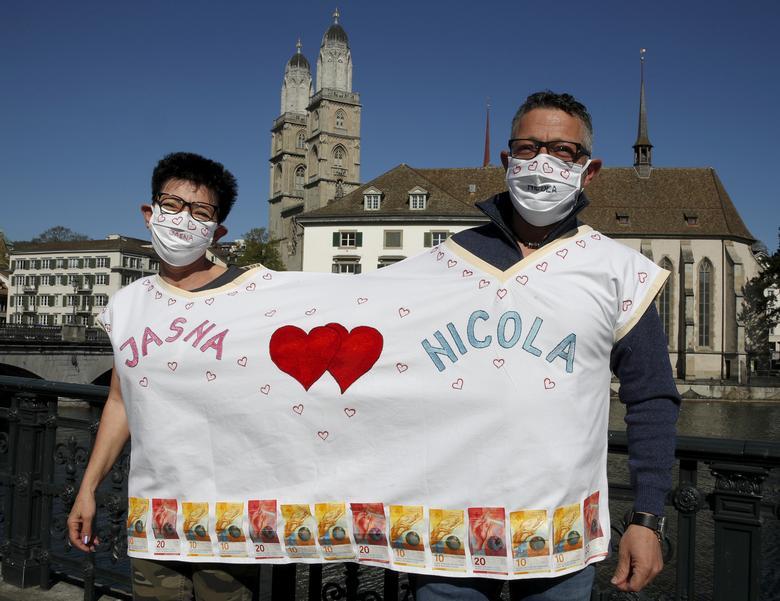 Jasna và Nicola Boccella đeo mặt nạ bảo vệ khi họ tạo dáng sau lễ cưới trước nhà thờ Grossmuenster ở Zurich, Thụy Sĩ hôm 14/4.