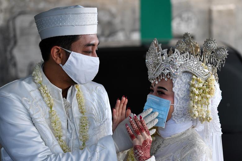 Chủ rể người Indoesia mang găng tay, đeo khẩu trang cho cô dâu khi họ tiến hành hôn lễ tại văn phòng tôn giáo ở địa phương. Đám cưới cũng rất vắng người vì dịch bệnh đang lây lan rộng.