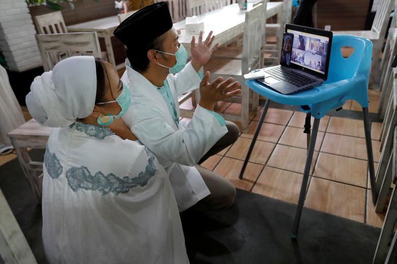 Mohamad Nurjaman và Ugi Lestari Widya Bahri chào các thành viên gia đình của họ thông qua một cuộc họp video sau lễ cưới ở Tangerang, ngoại ô Jakarta, Indonesia,