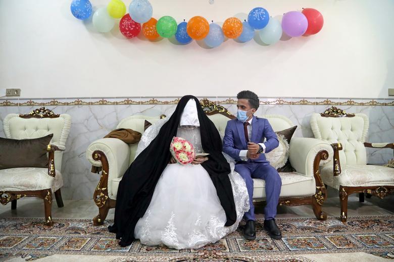 Một cặp vợ chồng người Iraq tiến hành hôn lễ trong giờ giới nghiêm của đất nước. Chú rể, cô dâu đều phải đeo khẩu trang trong thời điểm dịch bệnh đang diễn biến phức tạp.