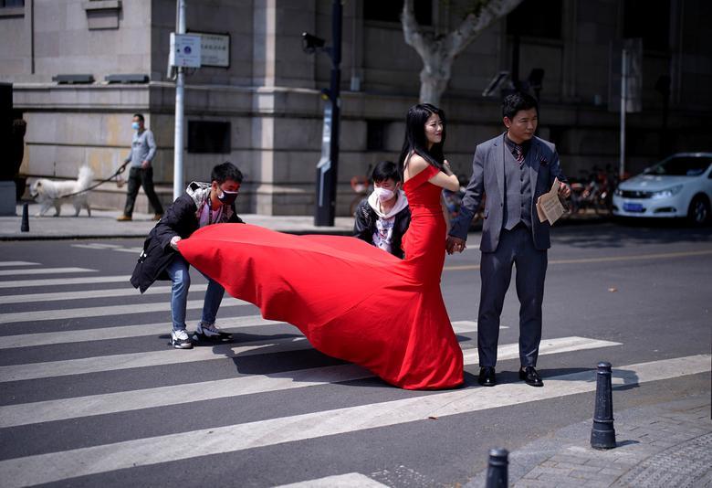 Một cặp tình nhân chụp ảnh cưới tại Vũ Hán sau khi lệnh phong toả (được tiến hành vào tháng 1/2020) được gỡ bỏ. Họ vui mừng khi dịch bệnh đã được kiểm soát, giúp ngày vui