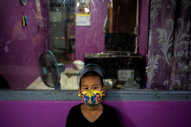 Một cậu bé ở Băng Cốc, Thái Lan đeo khẩu trang to đùng, che gần hết cả phần mặt. Chiếc khẩu trang được may từ vải quần áo, có hoạ tiết hoạt hình vui nhộn, dễ bắt mắt trẻ nhỏ.