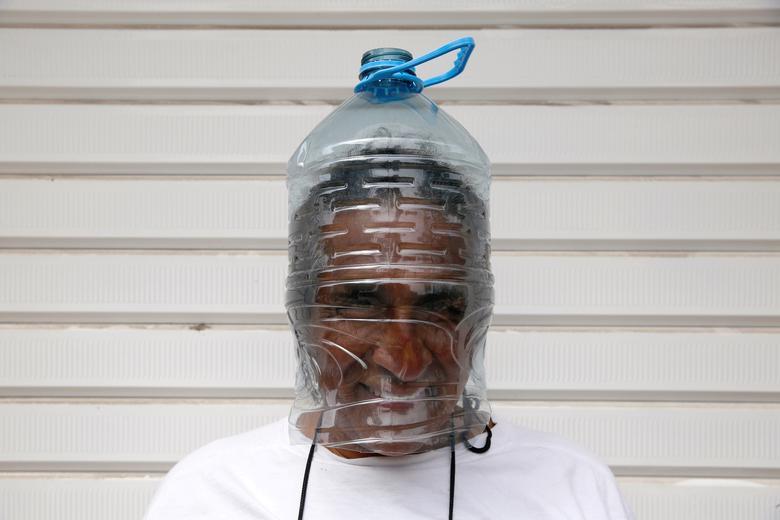 Một người đàn ông tự chế khẩu trang bằng bình đựng nước trước khi lên máy bay trở về Canada tử Peru, trên chuyến bay do Đại sứ quán Canada tổ chức cho công dân bị mắc kẹt tại Peru.
