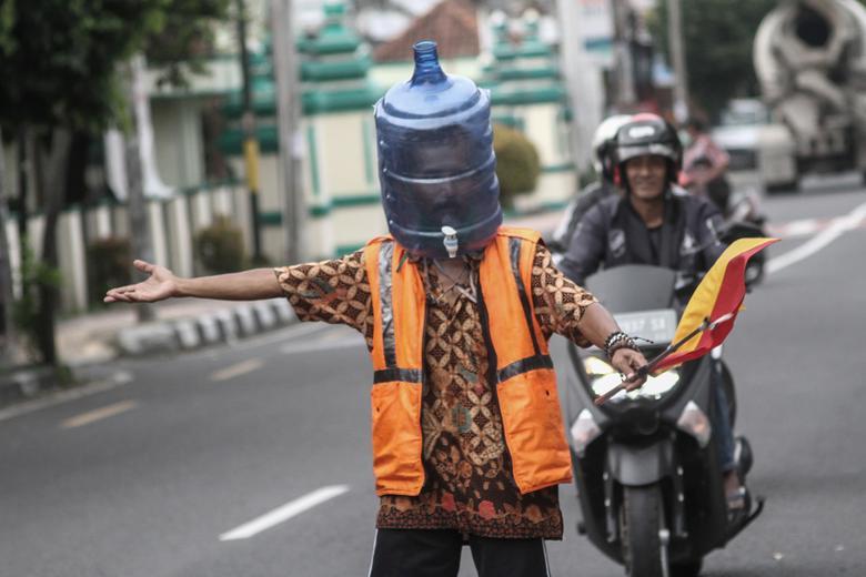 Ali Akbar, một nhân viên giữ xe ở Yogyakarta, Indonesia cũng dùng thùng nước làm khẩu trang.