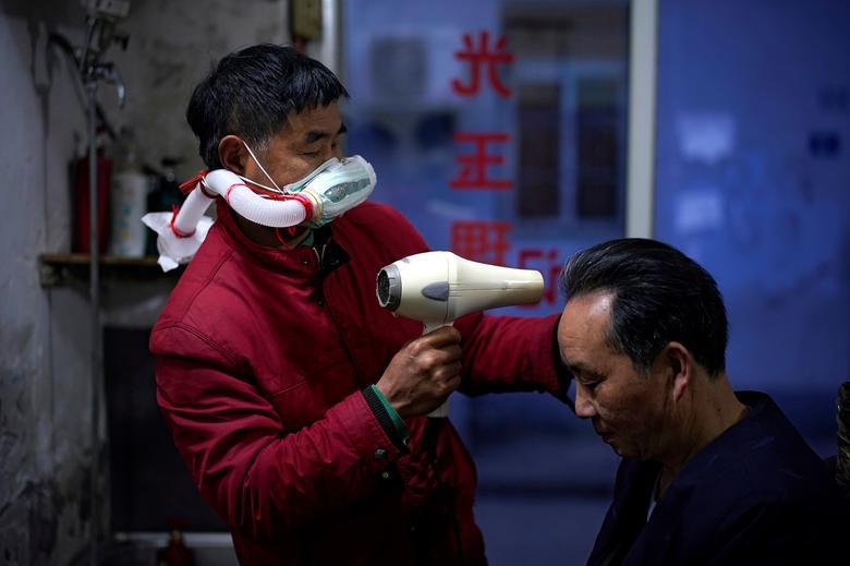 Yang Guangyu, 54 tuổi, một thợ cắt tóc ở Vũ Hán dùng chai nhựa, ống dẫn nước để làm khẩu trang tự chế. Hiện, cửa hàng của anh đã mở cửa trở lại cắt tóc cho nhiều người.