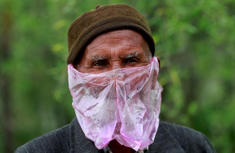 Người đàn ông ở Srinagar, Ấn Độ phải dùng túi nilon để làm khẩu trang vì không có tiền mua.