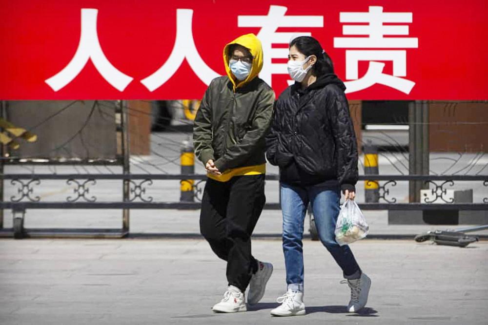 """Người dân đi bộ trước tấm bảng tuyên truyền """"mọi người đều có trách nhiệm (kiểm soát sự lây lan của dịch bệnh)"""" tại một công viên công cộng ở Bắc Kinh vào thứ Ba 21/4 - Ảnh: AP"""