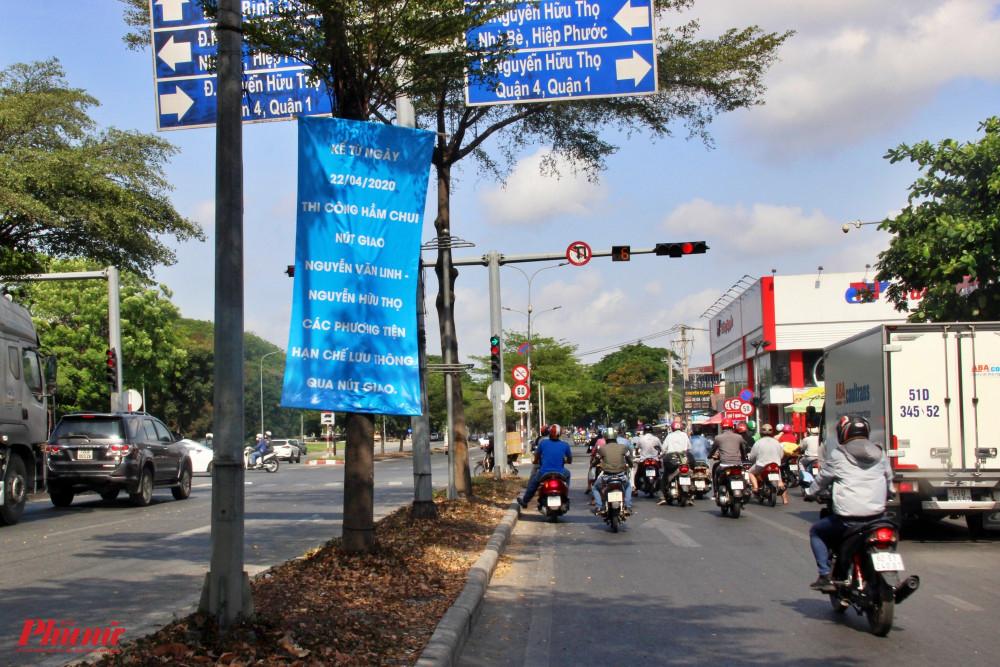 Đơn vị thi công treo băng rôn thông báo các phương tiện hạn chế lưu thông qua nút giao Nguyễn Văn Linh - Nguyễn Hữu Thọ